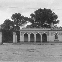 Image: Single-story stone building with a veranda featuring four archways. To the left of the building is a large metal gate with lights on top of the gate posts and a flag pole.