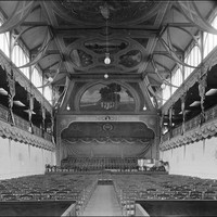 Image: rows of chairs face a stage area at the far end of a large hall. The hall's end wall and roof are decorated by painted murals.