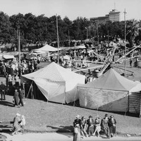 Image: a spinning carnival ride set up in a park is surrounded by a number of large canvas tents and a crowd of people in 1930s era clothing