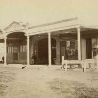 Image: A line of shops with verandahs lining a dirt road.