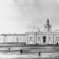 Image: a single storey public building with a small flight of stairs leading up to an arched entrance and a cupola with a domed roof and weather vane.