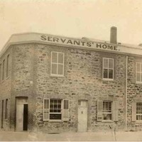 """Image: A simple two-storey stone building with three main entrances, one on a corner, shuttered windows and a parapet sign reading """"Servants' Home""""."""