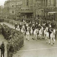 Image: a group of men in military dress uniform riding white horses parade past lines of soldiers and a crowd of civilians. Other groups marching under banners follow behind.