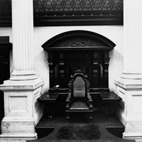 Image: a single chair sits on a small podium, located between two white columns and backed by carved wood panelling with a desk/shelf on either side the chair.