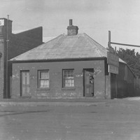 Image: a small semi-detached cottage with tin roof, rear lean-to and central chimney. Each residence has a door and single window on the front side of the house. A figure stands in the open door of one side of the building.