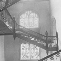 Image: A staircase with intricate windows in the background