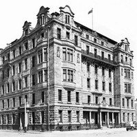 Image: an imposing six storey stone building with bay windows, a columned portico, balconies, mansard roof, curved parapets and a flagpole on the roof stands on the corner of two roads. A 1920s era car can be seen to the right of the photo..
