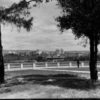 Image: a man stands behind a stone balustrade atop a low hill looking out over a city and a cricket oval with a grandstand