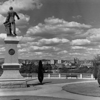 Image: a statue of a man holding a map stands on a plinth on a hill surrounded by formal gardens and overlooking a city
