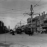 Image: electric trams travel down a wide city street lined with two and three storey buildings. A large, ornate lamp post can be seen in the centre of the image.