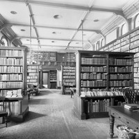 Image: a small library with leather bound volumes on tall wooden shelves. Most of the shelves line the walls but there are several rows protruding into the room from both sides. The room has a patterned carped and has desks and chairs scattered throughout