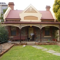 Image: A man and his dog stand outside a bluestone building with red brick quoins around its windows and two red brick chimneys. The building also has a red tin roof, simple wooden verandah and a gable with decorative moulding painted in cream and taupe.