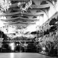 Image: a large hall with a second storey gallery running around the edges and an intricate ceiling is decorated by large displays of flowers arranged to look like blossoming trees. On the far wall is a sign reading God Save the King.