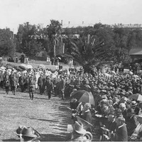 Image: a large crowd of people in early 20th century dress, some with umbrellas, stand on a grassed area in a park watching men in military uniform parade.