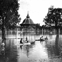 Image: A boy stands in waist deep water in a flooded park while others sit in row boats around him. In the centre of the photograph is a rotunda which is half underwater.