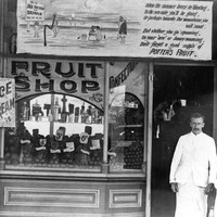 Image: A man and young girl in early 20th century clothes stand outside a fruit shop. The building is covered with advertising including that for icecream and cool drinks