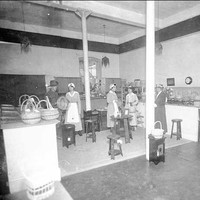 Image: Four women, two of them wearing aprons, and a man in a military uniform stand in a room with a number of woven baskets sitting on a bench.