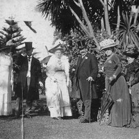 Image: A small group of well-dressed men and women stand on a lawn in front of trees