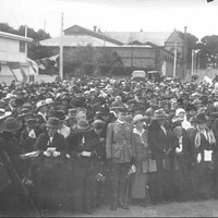 Image: a large group of men and women, some holding pamphlets, stand in front of a white building at a memorial ceremony.