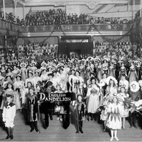 Image: A large group of women and children wearing flower costumes stand in an large open room with a sign reading English Dandelion while in the gallery above them men and women look on