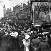 Image: men in dark suits parade under banners past a large crowd