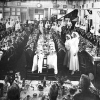 Image: men in naval uniforms are seated around long tables with white cloths being served food by women in white dresses