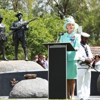 Image: woman at lectern speaking in front of sculpture