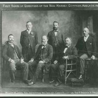 Image: black and white shot of six men, four are sitting and two are standing