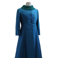 Image: peacock blue sparkling coat, long sleeves and skirt