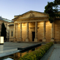 Image: The front of a large stone building with six columns flanking the entrance. A fountain and benches are arranged along stone sidewalks in front of the building