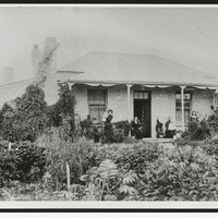 Image: people standing on verandah of small building