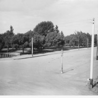 Image: One corner of a large park. A street with a lone gaslight lamp is visible in the foreground