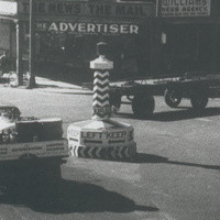 Image: Various mid-twentieth century auto-mobiles pass through an intersection in an urban area. A large plinth stands in the centre of the intersection and is marked with the words 'Keep Left' and left-facing arrows