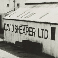 Image: Three lines of early twentieth century harvesting machines are positioned adjacent to a light-coloured building with the words 'David Shearer Ltd.' painted on its side