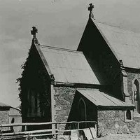 Image: A stone church with a steep peaked roof stands in an open expanse of flat ground