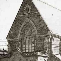 Image: A large bluestone church is surrounded on three sides by a picket fence and borders a road. Electric trolley lines are visible in front of the church