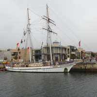 Image: A two-masted sailing ship is tied up alongside a long concrete wharf. A mix of old and modern buildings are visible in the background