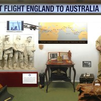 Image: display featuring map, manequin in flight gear and statue of four men