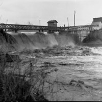 Image: A torrent of flood water pours through a weir along a river. Deep flood waters are visible flowing downstream in the foreground, and a group of men watch the flood from the top of the weir