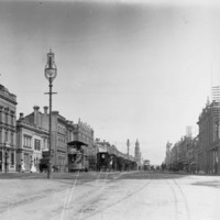 Image: black and white photograph of city street, with tram, horse drawn vehicles and pedestrians