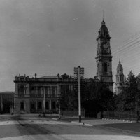 Image: A large, two-storey stone building with a tall clock tower protruding from one corner. A tree-lined park with wrought-iron fence is visible in the right foreground