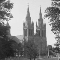 Image: A man in a suit and hat reclines on the grass in a park. A large stone church with twin spires is a prominent background landmark