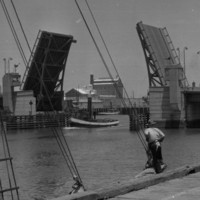 Image: A drawbridge within an active port is open to allow a tug to pass beneath it. A wharf with two mid-twentieth century sailing vessels tied alongside it is visible in the immediate foreground