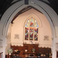 Image: An large, interior room with a high ceiling, wooden pews and a large stained glass window