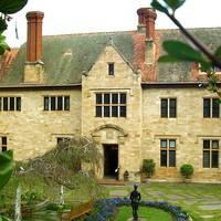 Image: The front of a large, two-storey stone mansion. A garden with benches and statuary is in the middle-foreground