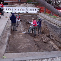 Image: large hole in the ground with people standing in the bottom and above