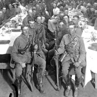 Image: large group of men in army uniform seated at tables in hall