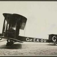 Image: black and white photo of bi-plane on the ground