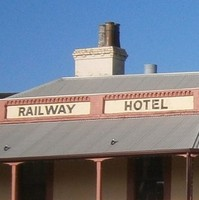 Image: A two-storey Victorian-era building with the words 'Railway Hotel, 1856' painted just below the roof