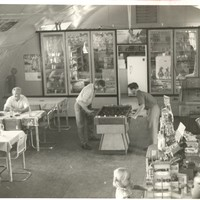 Image: interior of building with curved roof, people at game table